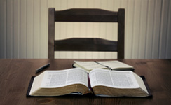 Bible, pen, and paper on table